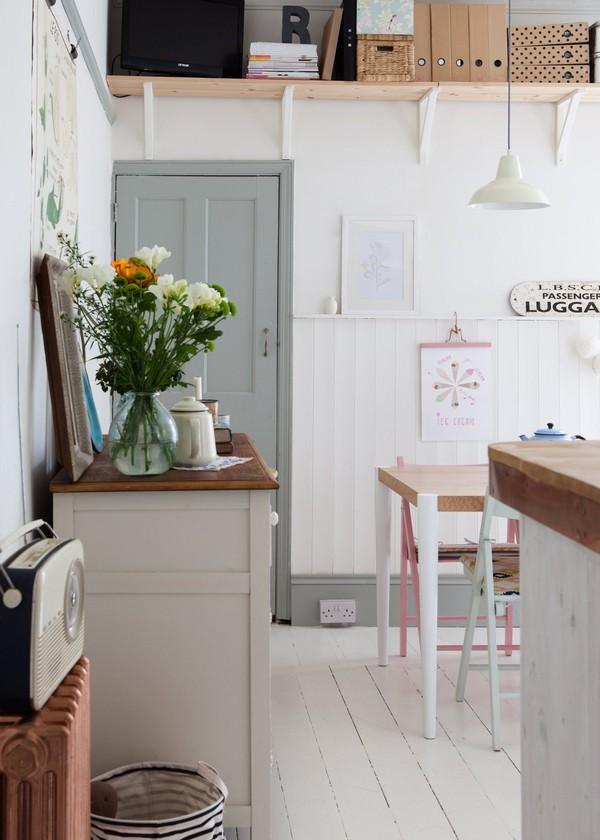 Từ nhà bếp hướng ra hành lang, giữa không gian trung hòa trong hai sắc trắng và xám, lọ hoa thủy tinh cắm sơ sài chính là điểm nhấn hữu ý.